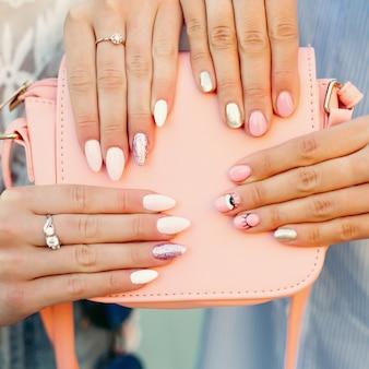 革のピンクの袋を保持しているデザインのマニキュアを持つ2人の女性。