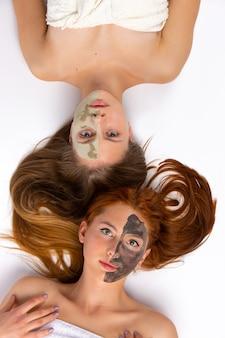 얼굴의 절반에 얼굴 마스크를 가진 두 명의 여성이 건강한 피부와 미용 개념을 바닥에 누워 있습니다.