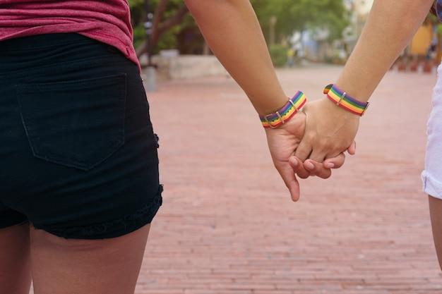 Two women with lgtb bracelets. lgbt concept