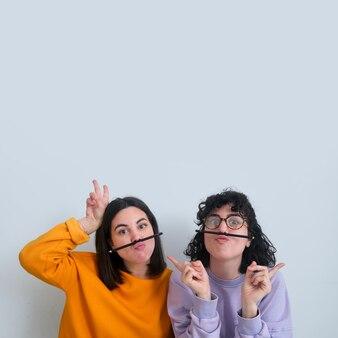 口ひげとして鉛筆を持つ2人の女性