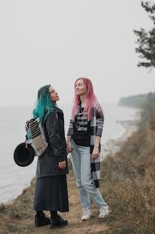 ピンクと青の髪の2人の女性が手をつないで笑っています