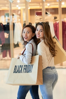 Two women with plastic bags on shopping spree