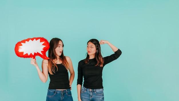 Due donne con discorso palloncino parlando