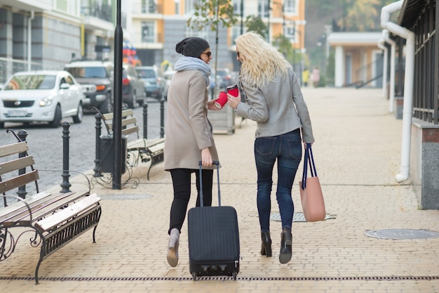 Two women with suitcase walking along city street