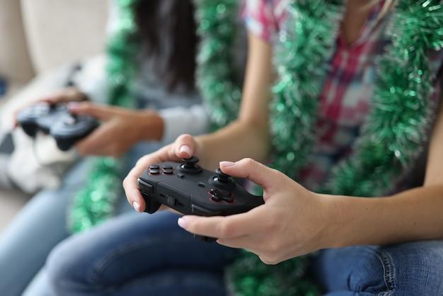 Two women with tinsel around their necks are holding joysticks