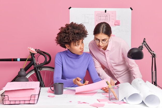 Two women work together on project makes schemes discuss something while looking in paper pose at desktop with serious expressions prepare project of company development. female designers at work