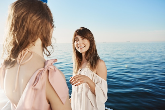 Two women on yacht sailing in sea, having conversation about their great plans for vacation.