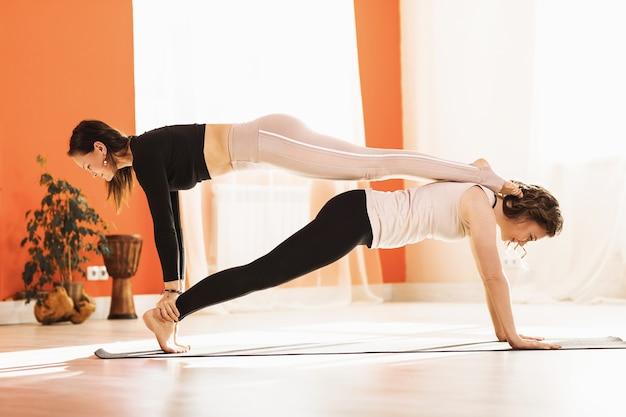 두 명의 여성 요가 수련생이 한 사람과 다른 사람 위에 kumbhakasana 쌍 운동을 수행합니다.