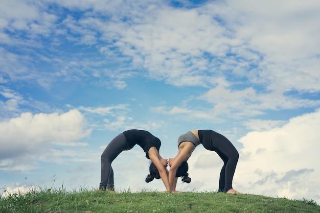 Two women do yoga urdhva dhanurasana or chakra-asana in the park on sunny day beautiful sky.