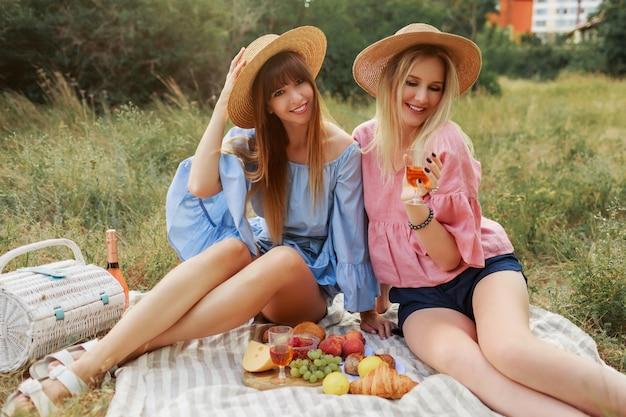 Две чудесные девушки в соломенной шляпе проводят каникулы в сельской местности, пьют игристое вино.