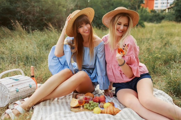 Two wonderful girls in straw hat spending holidays in countryside, drinking sparkling wine.