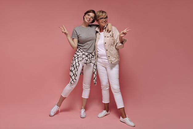 Две прекрасные женщины с короткими волосами и в современных очках в белых узких брюках и легких кроссовках улыбаются и демонстрируют знаки мира на розовом фоне.