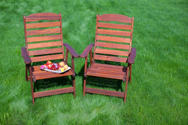 Two wood chairs on the grass with vase of flowers