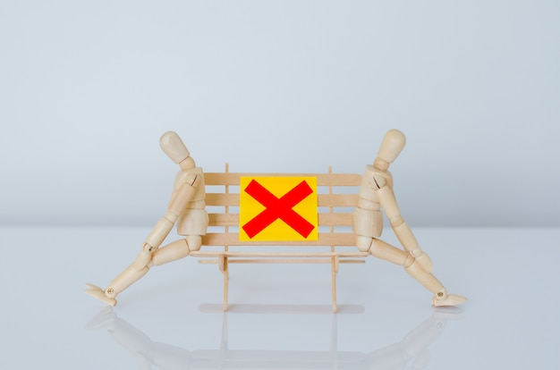 Two wood models sitting on bench and keep distance with the gap to protect infection of coronavirus or covid-19. new normal and social distancing concept.