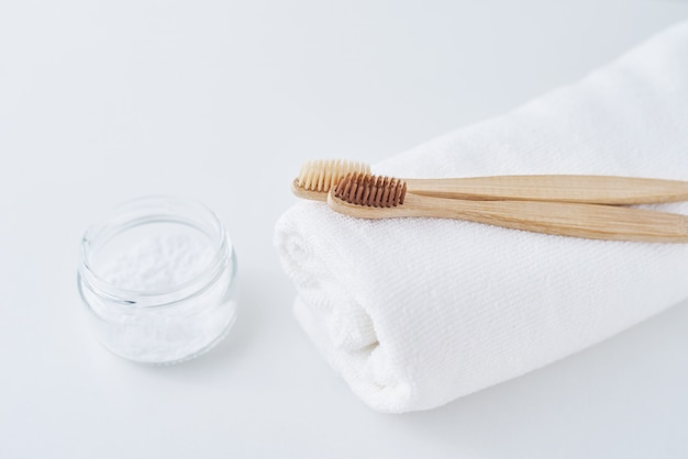 Two wooden bamboo eco friendly toothbrushes on towel and baking soda on white,  dental care concept