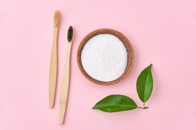 Две деревянные бамбуковые зубные щетки и пищевая сода на розовом фоне. экологичные зубные щетки, безотходная концепция