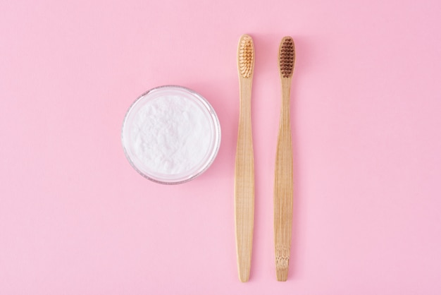 Two wooden bamboo toothbrushes and baking soda powder in glass jar.  teeth health and keep mouth concept