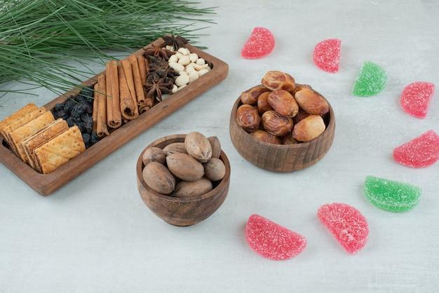 말린 과일과 견과류 흰색 바탕에 두 개의 나무 그릇. 고품질 사진