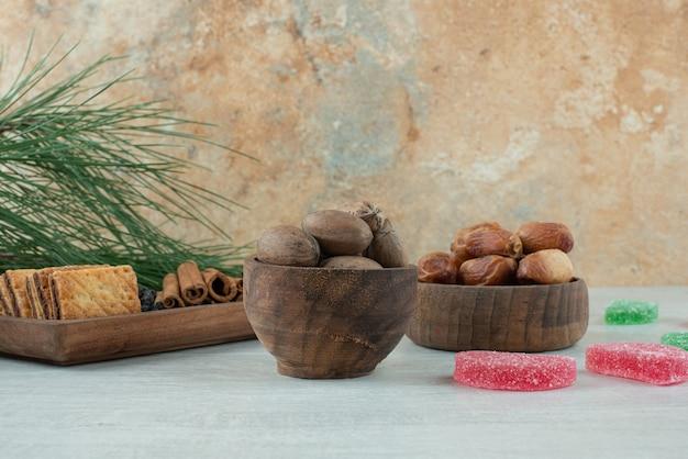 Две деревянные миски с сухофруктами и орехами на белом фоне. фото высокого качества