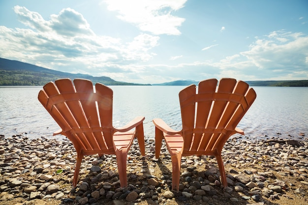 물에 직면 호수 기슭에 두 개의 나무 의자.