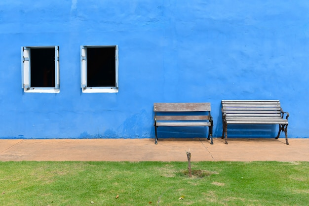 Two wooden chairs set in front of the blue plaster wall