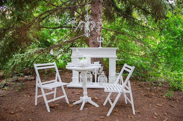 Two wooden chairs and a table in the backyard with flowers and tea equipment.