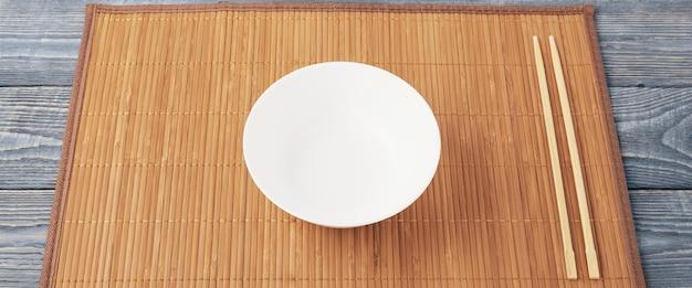 Две деревянные палочки для еды и белая чашка на бамбуковой циновке