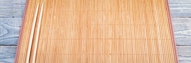 Two wooden chopsticks on a bamboo mat