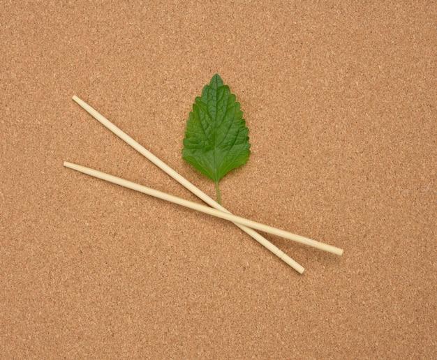 Две деревянные палочки для еды на коричневой поверхности, без отходов, вид сверху