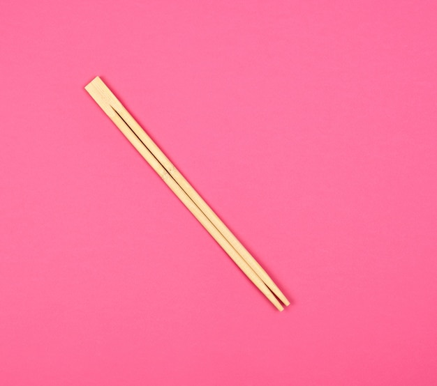Two wooden chopsticks on pink