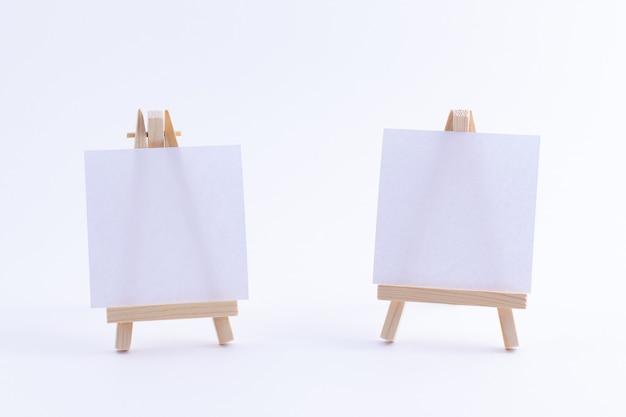 空白の白い正方形のキャンバスと2つの木製イーゼルミニチュア