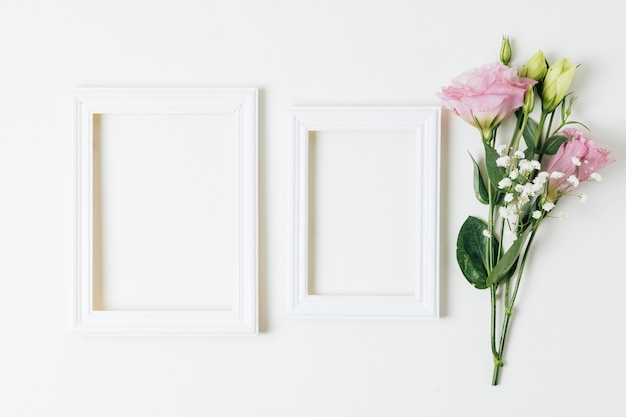 Two wooden empty frames near the pink eustoma and baby's-breath flowers on white background