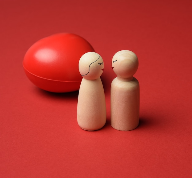 Two wooden figures on a red heart background, kiss and love