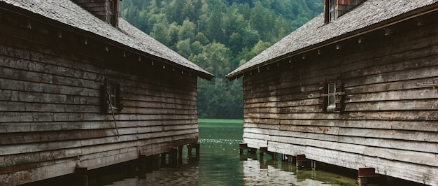 Two wooden gray houses on the water in the wooded alpine mountains of austria.