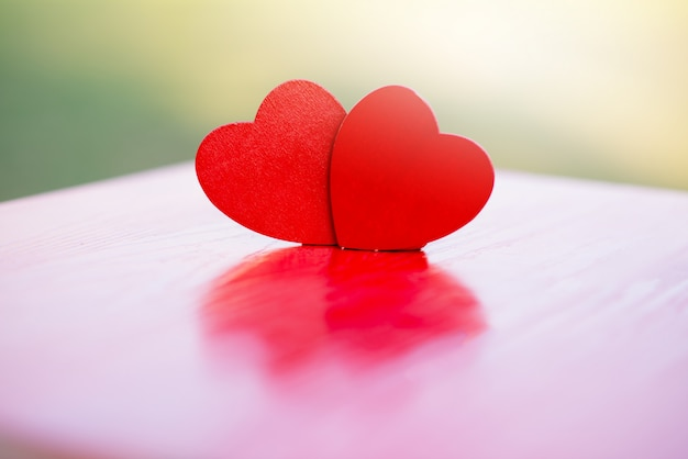 Two wooden hearts on a red wooden table blurred , love expression, valentine festival, love concept