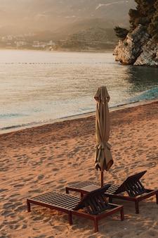두 나무 의자와 섬 근처 몬테네그로에서 석양 모래 해변에 우산
