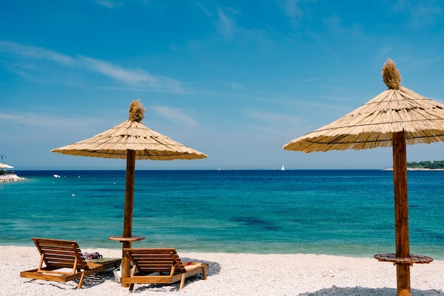 크로아티아 프리모 스텐 마을 근처의 파라다이스 해변에 하얀 모래에 두 개의 나무 의자