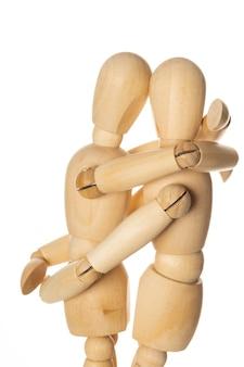 Два деревянных манекена, обнимая друг друга на белом фоне
