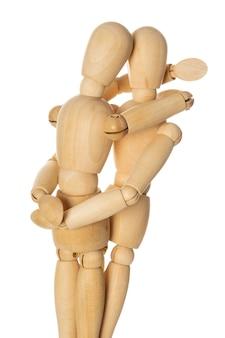 白い背景の上でお互いを抱き締める2つの木製のマネキン