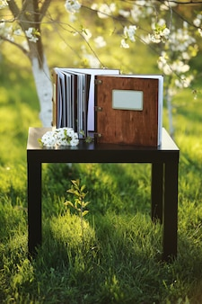 Two wooden photo books on the table in the nature. place for the inscription
