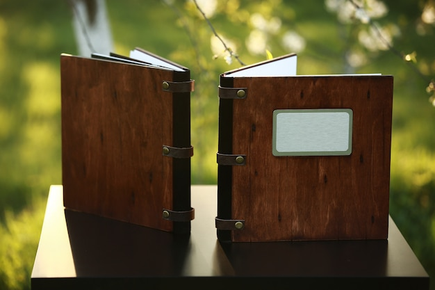 Two wooden photo books on the table in the nature.