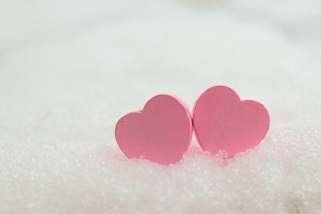 白い雪の背景のクローズアップに2つの木製のピンクのハート。バレンタインデーと愛のコンセプト。