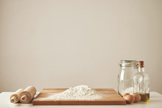 Две деревянные скалки, оливковое масло первого отжима, прозрачная банка и деревянная разделочная доска с белой мукой, изолированные куриные яйца. все подготовлено для замеса теста