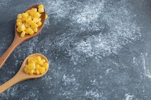 Due cucchiai di legno di mais dolce su marmo.
