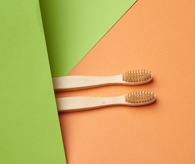 Две деревянные зубные щетки на зеленом оранжевом фоне,