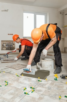 Two workers are installing ceramic tiles on the floor