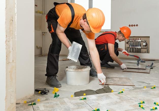 Двое рабочих кладут на пол керамическую плитку.