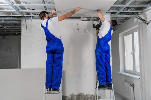 Двое рабочих делают потолок из гипсокартона. они используют дрель и лестницы