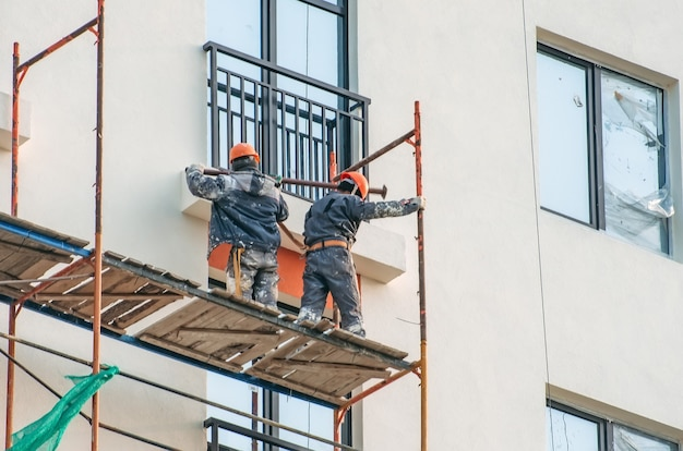 Two workers assembling scaffolding on city building.