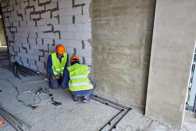 Two workers or builders in protective clothing and orange hard hats installing plastic pipes using modern tools in flat of building under construction
